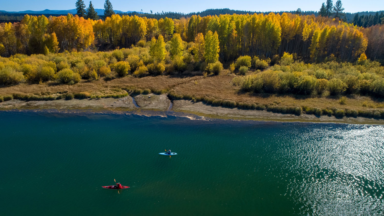People lackadaisically kayaking down the calm Deschutes River